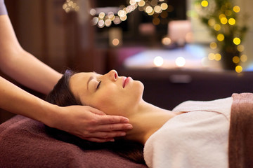people, beauty, lifestyle and relaxation concept - beautiful young woman lying with closed eyes and having face and head massage at spa