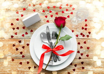 valentines day, table setting and romantic dinner concept - close up of red rose flower on set of dishes with cutlery, red rose, hearts and blank place card on wooden background