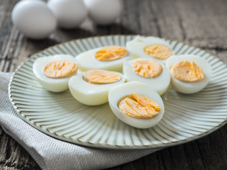 Boiled chicken eggs on a gray plate. Wooden background. The concept of Easter