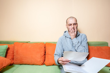 Young or middle age sick man in the casual clothes reading medical results on the papers from his doctor and realize that he have diagnosed a cancer or other sickness