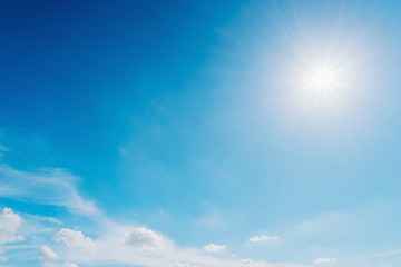 Blue sky with sun and clouds background.