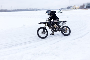 Biker motorcyclist riding on snow and ice in cold winter day. Extreme winter sport.