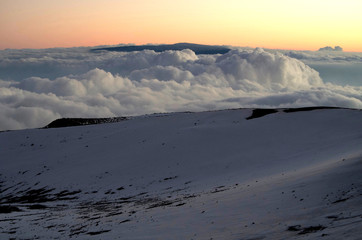 Sonnenuntergang, Aussicht vom Mauna Kea auf Mauna Loa Vulkan der sich durch die Wolken zeigt auf Big Island, Hawaii