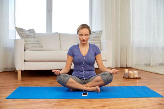 yoga, technology and mindfulness concept - woman with smartphone and earphones meditating in lotus pose at home