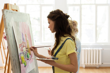 art school, creativity and people concept - woman with easel, palette and brush painting at studio