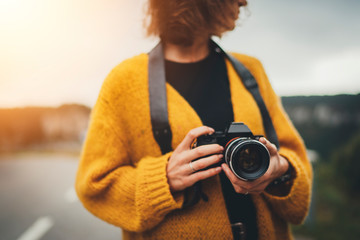 Closeup image of young hipster girl holding vintage film camera while traveling in Europe exploring amazing nature landscapes, Travel Discover Explore Concept
