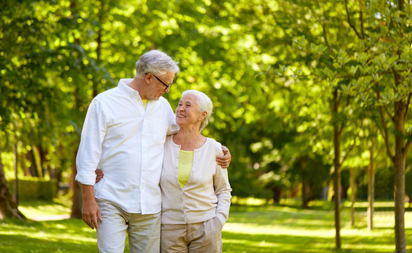 old age, relationship and people concept - happy senior couple hugging in city park