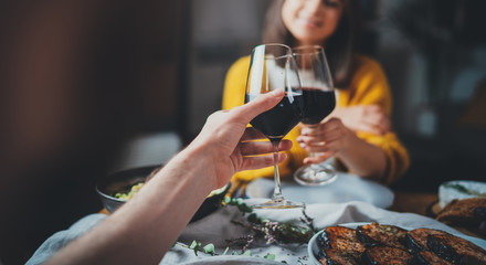 Cropped image of romantic couple making cheers with glasses of red wine during date in restaurant, Love Relationship Celebration Concept