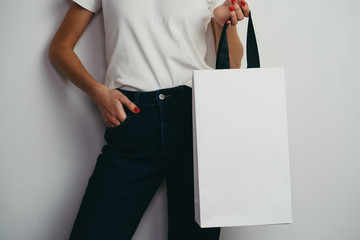 Cropped image of young hipster girl in blue jeans holding blank paper bag with black textile handles, mock up of white paper shopping bag with handles