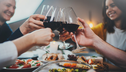 Group of happy friends celebrating anniversary at home making cheers with glasses of red wine, Dinner Family Holiday Friendship Concept