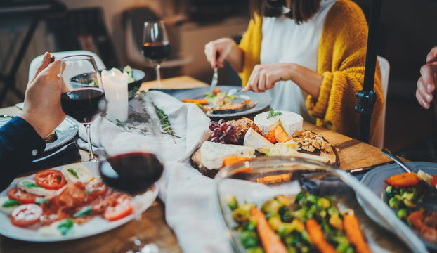 Group of friends enjoying healthy mediterranean food in restaurant, Young people drinking red wine in cozy home interior, Dinner Holidays Friendship Tasty Food Concept