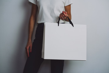 Young hipster girl wearing white t-shirt and holding blank white paper shopping bag, mock-up of white paper package, white background