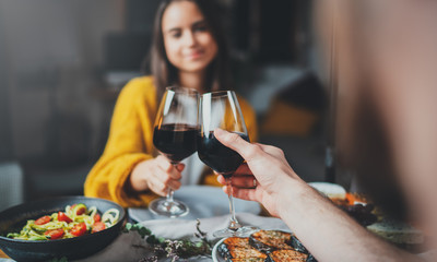 Young romantic couple making cheers with glasses of red wine in restaurant with healthy food, Relationship Celebration Love Date Concept, sweet couple dining together