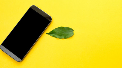 Wall Mural - smart phone and leaf on yellow background