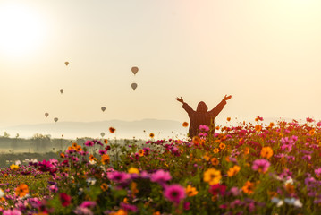 Lifestyle traveler women raise hand feeling good relax and happy freedom and see the fire balloon outdoors the nature tea and cosmos farm in the sunrise morning. Travel and summer Concept Wall mural