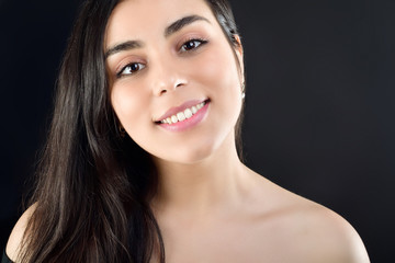 Portrait of a beautiful girl on a black background which is naked on the shoulders