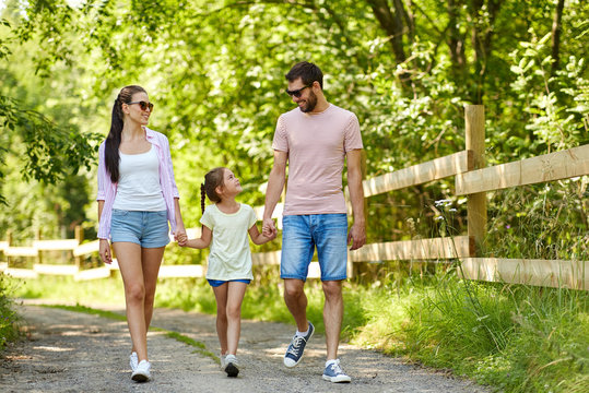 family, leisure and people concept - happy mother, father and little daughter walking in summer park