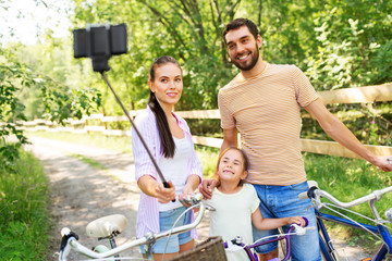 family, leisure and people concept - happy mother, father and little daughter with bicycles taking picture by smartphone selfie stick in summer park