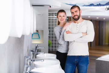 Young family couple choosing bathroom sink in store