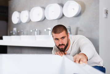 Man buyer choosing ceramic bath  in bathroom furniture shop