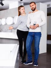 Smiling family couple choosing ceramic bath in bathroom fixtures shop