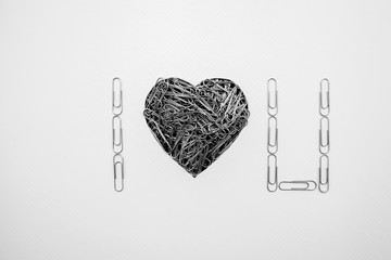Sentence I Love You including a heart shape made with paperclips on white background