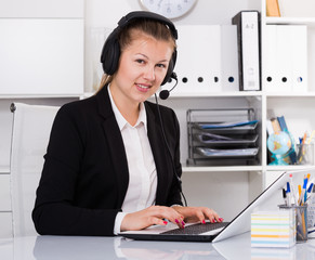 Dispatcher female in black suit is talking by headset with client