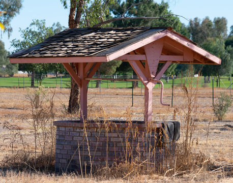 Decorative brick wishing well with shingle covered roof
