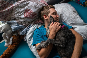 Young man sleeping and cuddling with his dog