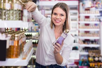 Cheerful attractive girl choosing new perfume at store