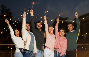 leisure, celebration and people concept - happy friends with sparklers at rooftop party at night