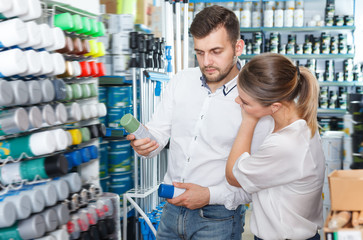 Adult man and woman choosing paint spray