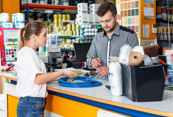 Young  man seller discussing with upset female customer  in tool-ware shop