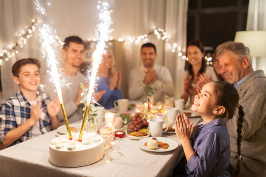 celebration, birthday and people concept - happy family having dinner party with fountain fireworks or sparkler candles burning on cake at home