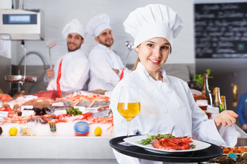 Attractive female chef with serving tray, offering dishes in fish restaurant
