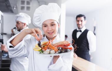 Female chef checking dish in fish restaurant