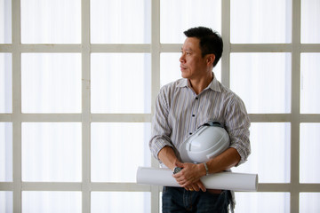 Portrait of male engineer with self-confidense and friendly manner, holding roll paper in hand