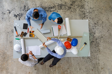 Group of four people including engineer and businessmen discuss and review about construction material, taken from bird eyes view