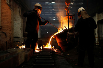 Foundry workers pour molten iron into moulds to create new mouldings, gutters and roof tiles to be used during the restoration of Britain's Houses of Parliament and the Big Ben clock tower at the Hargreaves Foundry in Halifax