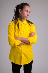 Young businessman with dreadlocks crossing arms and thinking