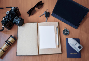 Notebook with pen, photo camera on wooden background