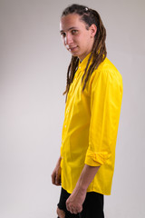 Profile view of young happy businessman with dreadlocks looking at camera