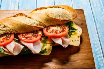 Long sandwich on cutting board on wooden table