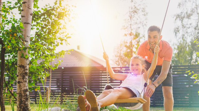 Joyous Father Pushes Swings with His Cute Little Daughter on Them. Happy Family Spends Time Together one Sunny Summer Day in the Idyllics Backyard.