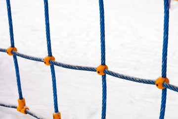 Fragment of  rope ladder on  background of snow.