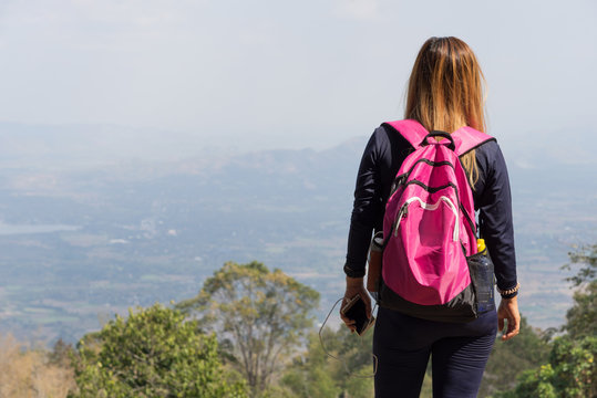 Asian woman with pink backpack looking at mountain view