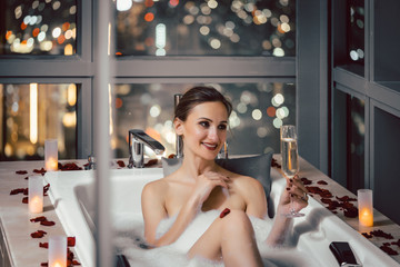 Woman bathing in expensive hotel or penthouse tub drinking champagne
