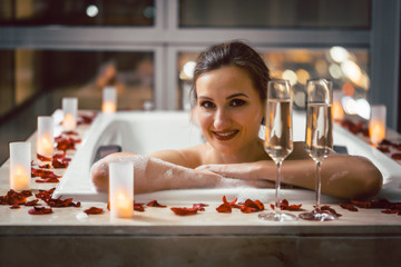 Woman waiting for her date with a second glass of champagne in expensive hotel or penthouse bathtub