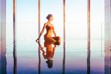 Woman in expensive indoor swimming pool of hotel or luxury apartment