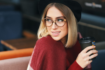 Portrait of romantic smiling woman holding coffee